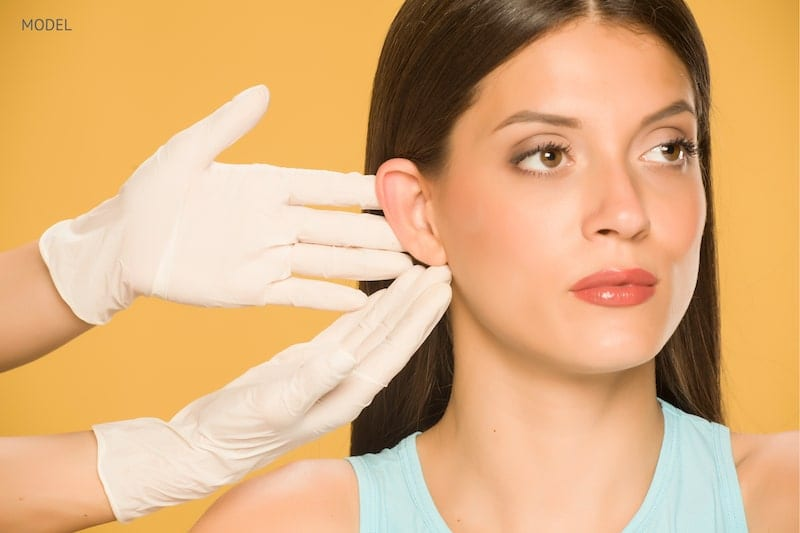 Doctor touching a woman's ear that they are about to pin back.