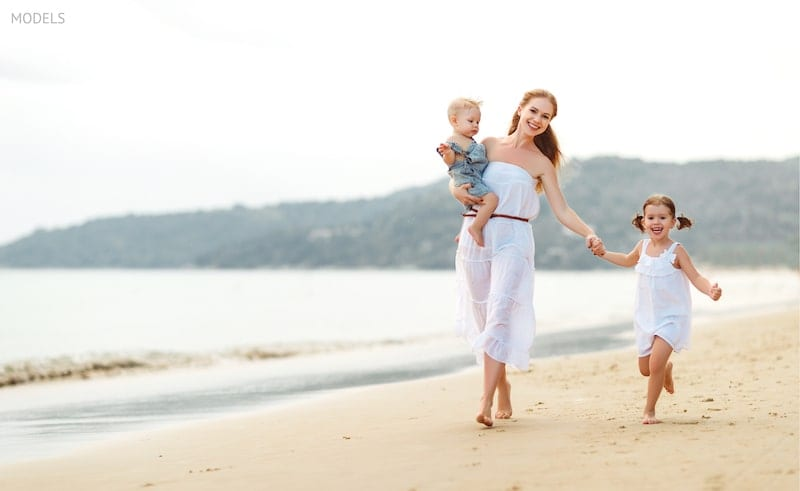 Mother walking along the beach with her children.