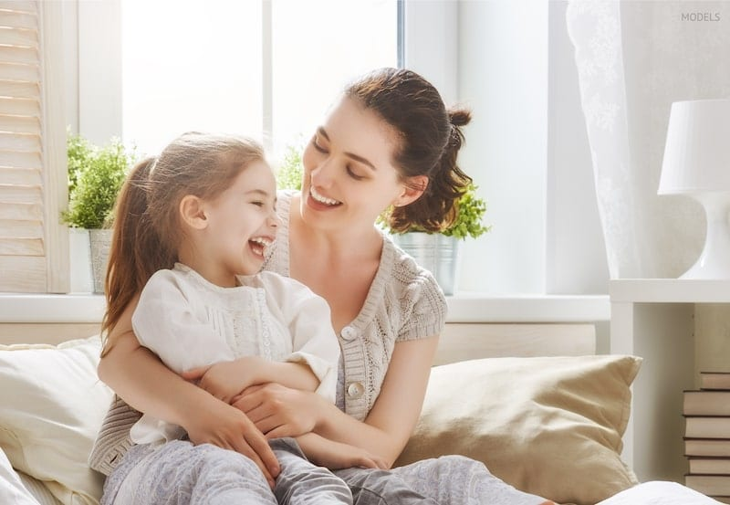 Young mother wrapping her arms around her young daughter, sitting on bed