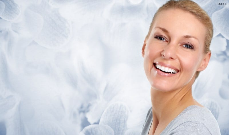 Smiling woman with pulled back hair standing in front of a blue, petal-like background.