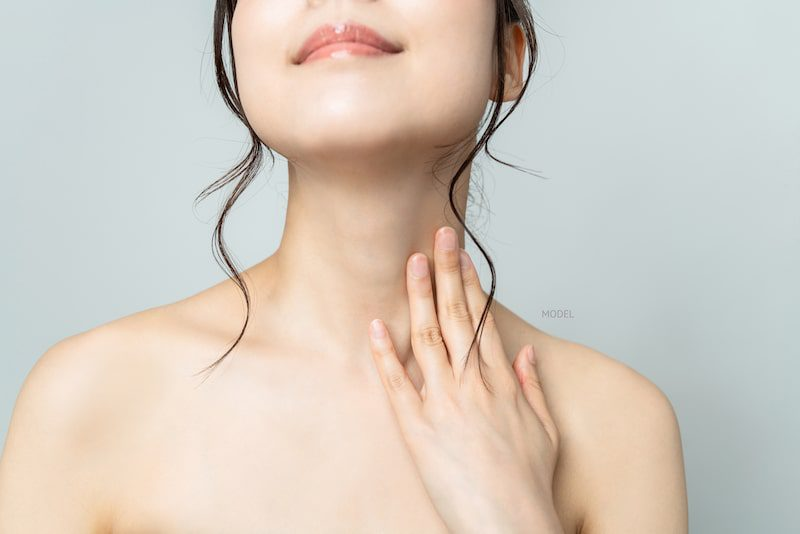 Close-up image of Asian woman's neck with her hand caressing her neck contours.